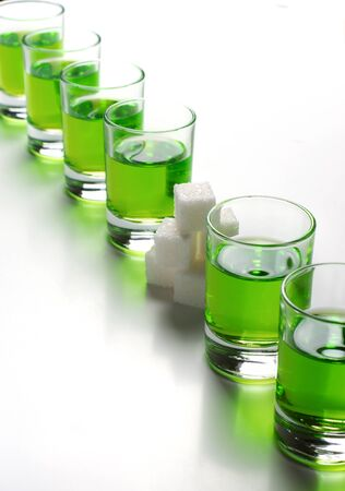 Absinthe green liquor in glasses. Alcoholic hallucinogenic beverage. White background. Pieces of white sugar.
