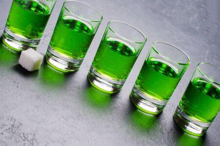 Absinthe green liquor in glasses. Alcoholic hallucinogenic beverage. Dark background. Pieces of white sugar