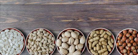 Assortment of nuts and seeds on wooden background. Pumpkin seeds, peanuts, hazelnuts, pistachios, pecans.