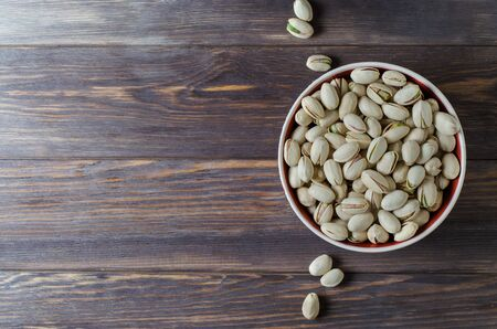 Pistachio nuts on the plate. Dark wooden background. Copy space
