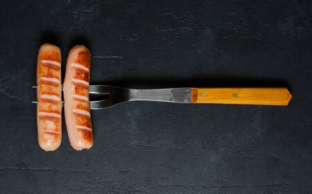 Grilled sausages fried on a metal fork. Unhealthy diet. Dark background