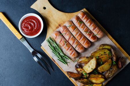 Grilled sausages on a wooden chopping Board. Fried potatoes, rosemary, tomato ketchup. Unhealthy diet. Dark background Stock fotó