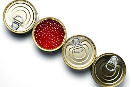 Red caviar of salmon fish. Four tinned metal cans. White background. Flat Lay. Copy space