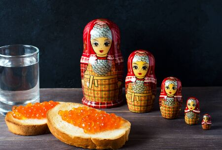 Sandwiches with red caviar of salmon fish. A glass of vodka, matryoshka. The concept of Russian tradition. Space for text
