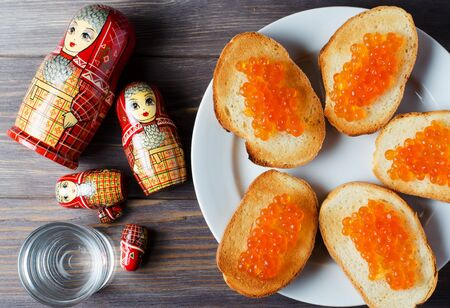 Sandwiches with red caviar of salmon fish. A glass of vodka, matryoshka. The concept of Russian tradition. Flat Lay Stockfoto