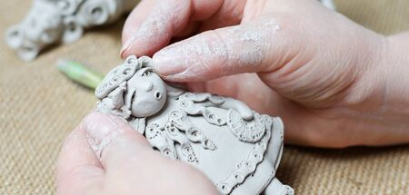 The process of making a souvenir doll made of clay. Female hands holding a toy made of clay.