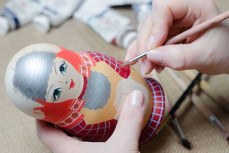 The artist draws a doll-matryoshka. Female hands with a brush close-up. Stock Photo