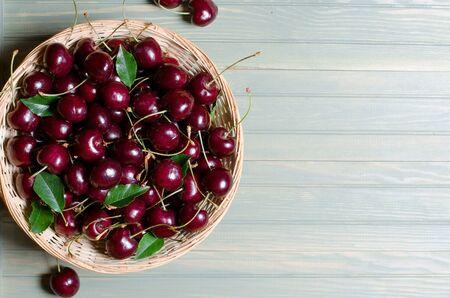 Lots of ripe red cherries in a wicker basket. Light wooden background.