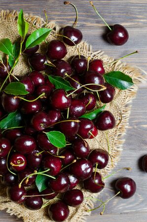 Cherries on the old fabric. Fresh crop. Rustic style. Wooden background.