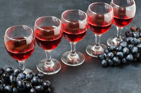 Red wine in glasses, a bunch of black grapes. Dark background