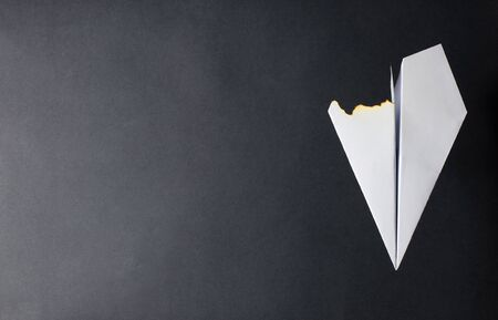 A paper plane with a burned wing. Dark background. The concept of a fire on the plane or the crash