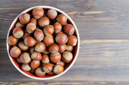 Hazelnuts in a white plate. Brown wooden background 写真素材