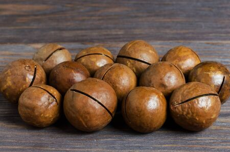 Macadamia nut on brown wooden background.
