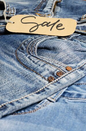 Denim. Blue jeans on the store counter. Sale - handwritten inscription on a paper label