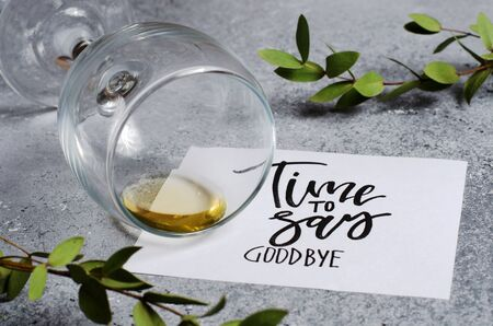 Time to say goodbye. The inscription on a white paper sheet. White wine in a glass glass. Concept - deterioration of relations between people. Stock fotó