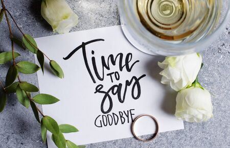 Time to say goodbye. The inscription on a white paper sheet. White wine in a glass glass. Gold engagement ring. Concept - deterioration of relations between people. Stock fotó