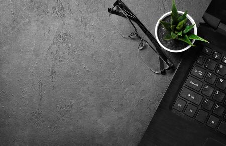 Working place for freelancers. Laptop, flower and glasses on a dark concrete