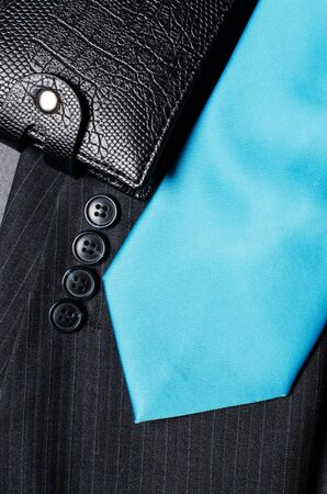 Blue mens necktie, jacket sleeve, and black wallet. Concept image of a successful business man