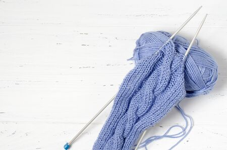 Balls of blue yarn and knitting needles. White background. Copy space. The concept of women 's needlework.
