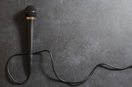 Black microphone on a dark concrete background. Equipment for vocals or interviews or reporting. Copy space