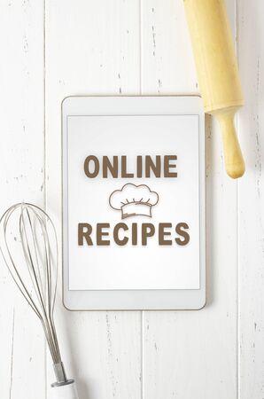 Online recipes. Cookbook in a tablet computer. Kitchen utensils. White wooden background