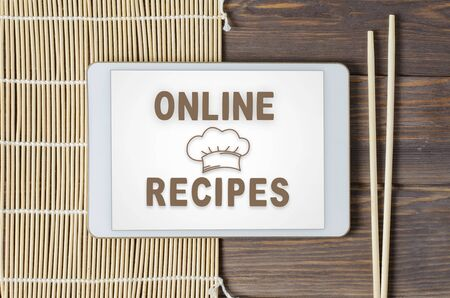 Online recipes. Cookbook in a tablet computer. Chopsticks and a bamboo tablecloth.Brown wooden background