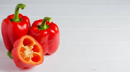 Three red ripe bell peppers. White wooden background. Copy space.