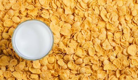Yellow background of corn flakes. Milk in a glass. Healthy and nutritious Breakfast. Copy space.