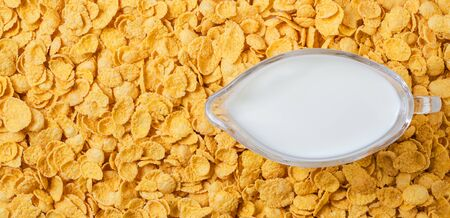 Yellow background of corn flakes. Milk in a jug. Healthy and nutritious Breakfast. Copy space.
