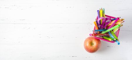 Childrens accessories for study, creativity and apple on a white wooden background. Back to school concept. Copy space