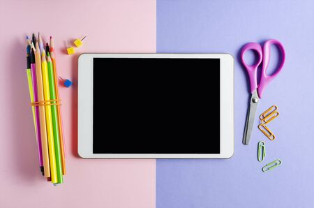 A tablet with an empty screen and office supplies on a colored background. Concept app for school children or online learning for children. Copy space