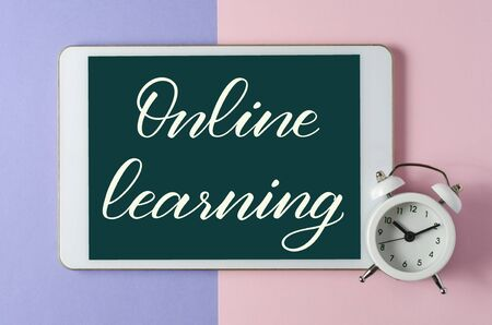 Online learning - handwritten inscription on a tablet. The concept of distance training for children. Tablet and white alarm clock on a colored background