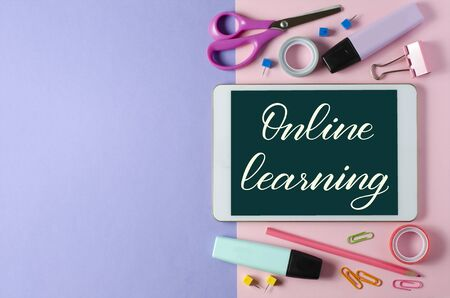 Online learning - handwritten inscription on a tablet. The concept of distance training for children. Tablet and office supplies on a colored background. Copy space