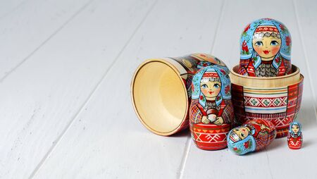 Five red matryoshka. Traditional Russian toy. Copy space. White wooden background Фото со стока