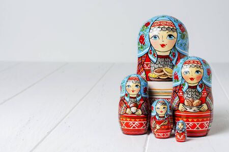 Five red matryoshka. Traditional Russian toy. Copy space. White wooden background.