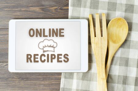 Online recipes. Cookbook in a tablet computer. Kitchen utensils. Brown wooden background.