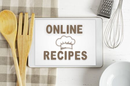 Online recipes. Cookbook in a tablet computer. Kitchen utensils. White wooden background. Фото со стока