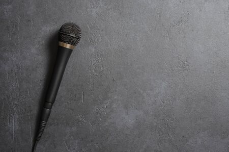 Black microphone on a dark concrete background. Equipment for vocals or interviews or reporting. Copy space.