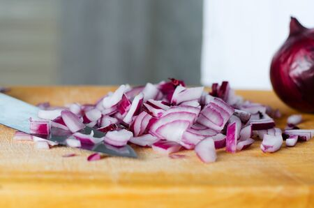 Red onion sliced. The process of cooking on a yellow cutting Board. Selective focus