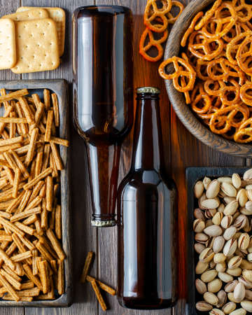 Beer in glass bottles and salty snacks for beer in wooden dishes. Rustic style. Brown wooden background. Фото со стока