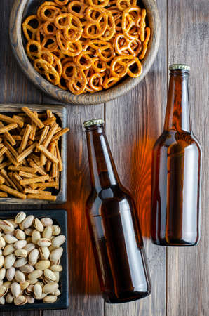 Beer in glass bottles and salty snacks for beer in wooden dishes. Rustic style. Brown wooden background 版權商用圖片