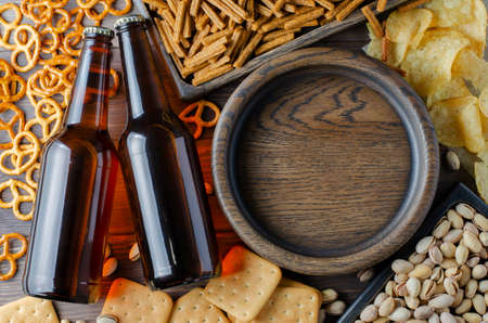 Beer in glass bottles and salty snacks for beer in wooden dishes. Rustic style. Brown wooden background. Copy space.