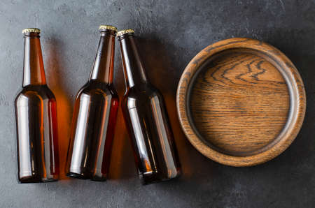 Beer in glass bottles and a wooden plate for snacks. Grey concrete background. Copy space.