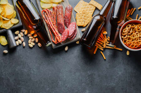 Beer in glass bottles, salty snacks for beer and sausages. Food and drinks for the party. Photo for a pub or restaurant menu. Free space for text