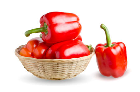 Paprika. Red bell peppers in a wicker basket. Isolated on a white background.