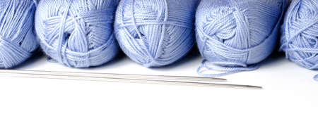 Balls of blue yarn and knitting needles. White background. Copy space. The concept of women's needlework.