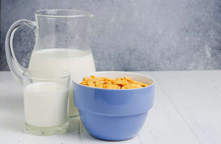 Corn flakes and milk in a glass jug. White wooden table. Copy space.