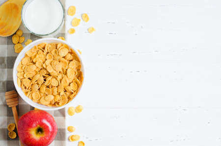 Corn flakes, milk, and an Apple on the tablecloth. Healthy and nutritious Breakfast. White background. Copy space.