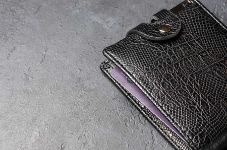 Black leather wallet . Dark concrete background. Copy space.