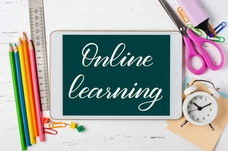 Online learning - handwritten inscription on a tablet. The concept of distance training for children. Tablet and office supplies on a white wooden background